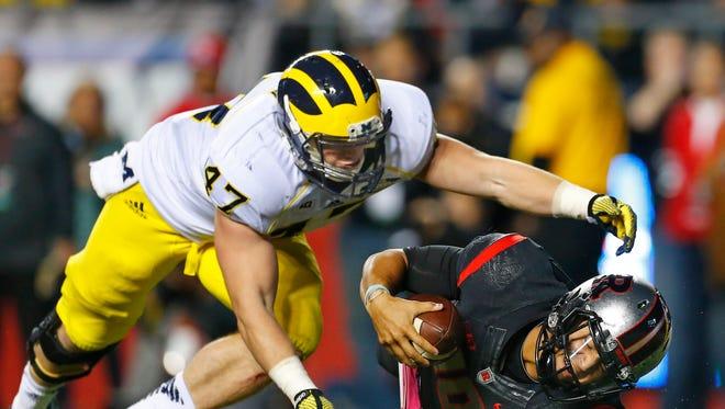 Rutgers quarterback Gary Nova (10) is sacked by Michigan's Jake Ryan (47).