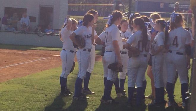 Jackson Christian's softball players gather for a team talk in front of their dugout between innings during their 2-0 win over Trinity Christian Academy on Tuesday.