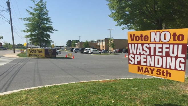 Signs supporting and opposing a proposal to borrow $20 million for constructing a new Milford High School are placed on the grounds of Lulu M. Ross Elementary School, a polling place for the school referendum, on Tuesday, May 5, 2015.