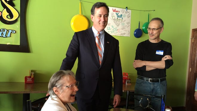 Presidential hopeful Rick Santorum meets with Marilyn Krocheski, a member of the Story County GOP, at Quirks Grill and Bar Sunday afternoon in Nevada.