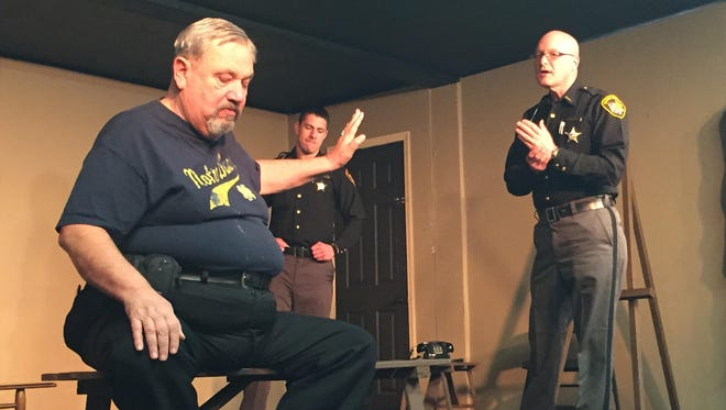 Retired Mansfield police Detective Gordon Wendling portrayed a man threatening suicide during the 2014 Crisis Intervention Team training as Richland County Sheriff's Office deputies Regnald Ganzhorn, right, and Chris Rahall talk him back to safety. The weeklong program, organized by Richland County National Alliance on Mental Health, teaches area law enforcement how to identify and handle calls involving people suspected of having mental illnesses.