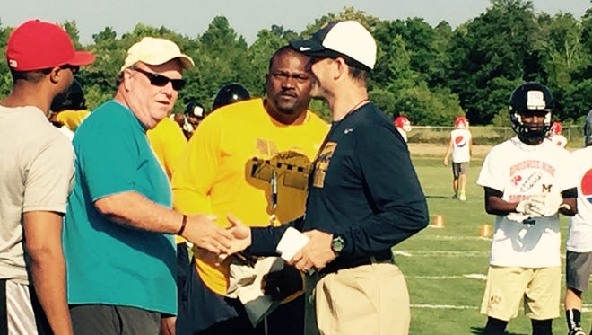 Michigan football coach Jim Harbaugh meets and greets during a camp Friday, June 5, 2015, in Prattville, Ala.