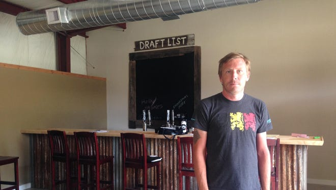 Jesse Prall, co-founder of Rubber Soul Brewing Co., stands in the taproom of Salisbury's newest brewery.