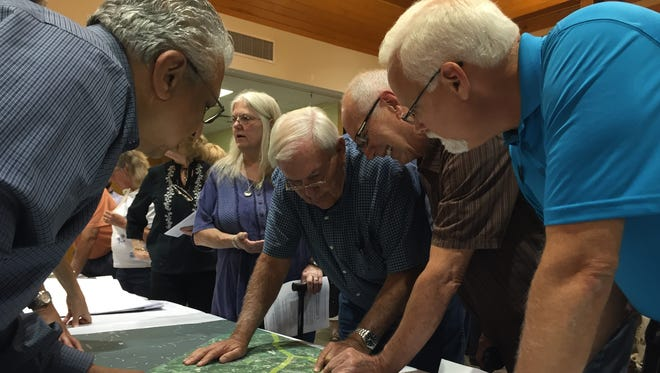 People looks over plans for Duke transmission lines at the WNC Ag Center Tuesday evening.