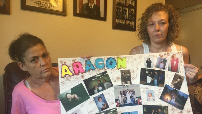 Nikki Askren, 46, and Lisa Askren, 42, hold up a poster of family pictures to be displayed at Friday's candlelight vigil.