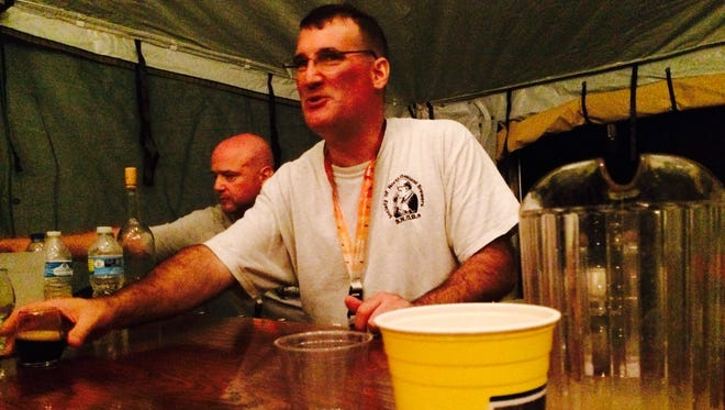 Home-brewer Bob Landry, 51, of Waterford offers his peanut stout to attendees Friday, Aug. 14, 2015 at the 6th annual Michigan Homebrew Festival.