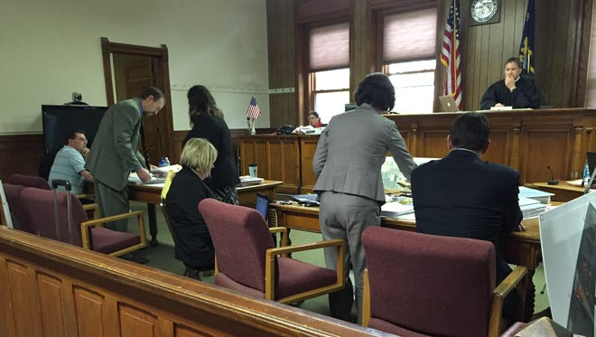 The parties involved in the Jaraczeski deliberate homicide case consult reports during a debate over statements made about the potential match of footwear impressions.