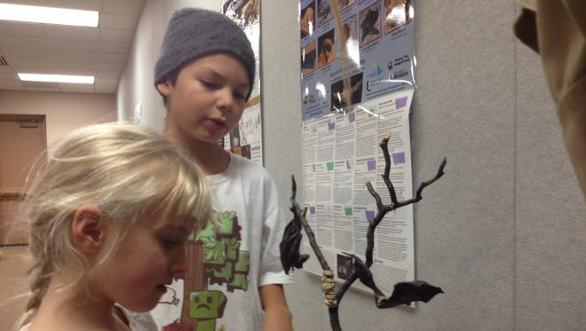 Ava Faner, 6, left, and Laydence Running Crane, 9, listen as Kim Linnell, conservation technician with Montana Fish Wildlife and Parks, explains the skeleton of a bat.