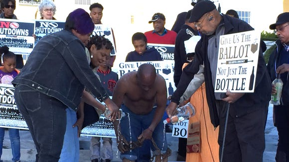 Protestors pour out the contents of liquor bottles into a metal pail at a rally at the Alabama State Capitol on November 23, 2015. The rally protested the attempted closing of part-time driver's license offices, noting that that state kept open money-losing ABC stores.