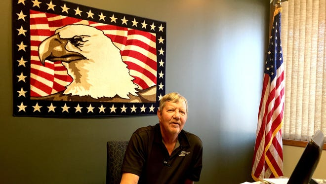Great Falls Chamber President Steve Malicott works in his office, which includes a U.S. flag and bald eagle drawing from his military days. While the military continues to be important in Great Falls, the community needs to keep diversifying its economy, he said.
