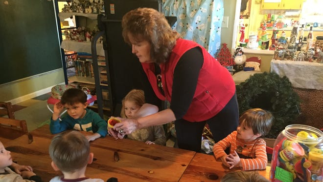 Carol Ross gives each child some Play-Doh to create an art project after lunch at Carol's Playhouse in Flippin.