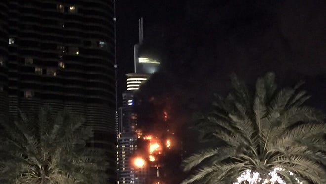 A fire runs up some 20 stories of a building in Dubai, United Arab Emirates, Thursday, Dec. 31, 2015.