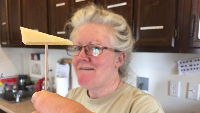 Fromagère Wendi Arnold holds up a sample of cheese made at Flathead Lake Cheese of Polson.