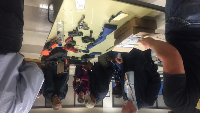 People look at a gun safe and gun safety locks on Thursday after the Alexandria Police Department's first responsible gun ownership class.