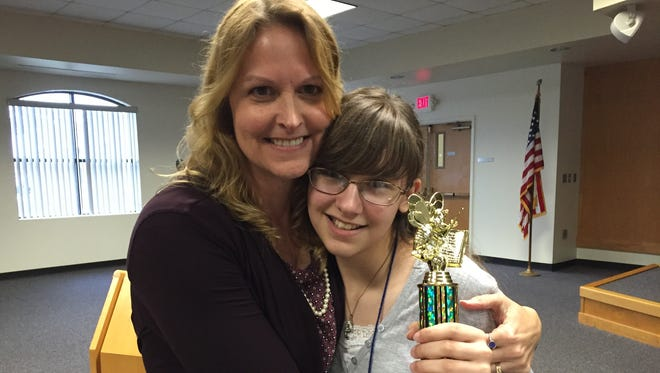 Kerra Paduano hugs her 13-year-old daughter, Anna, who placed first in the 57th annual Brevard County Spelling Bee.