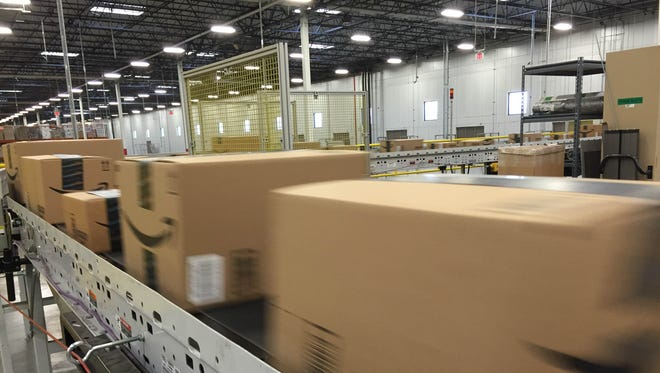 Packages whiz by on a conveyor belt at the Amazon fulfillment center in Tracy, Calif.
