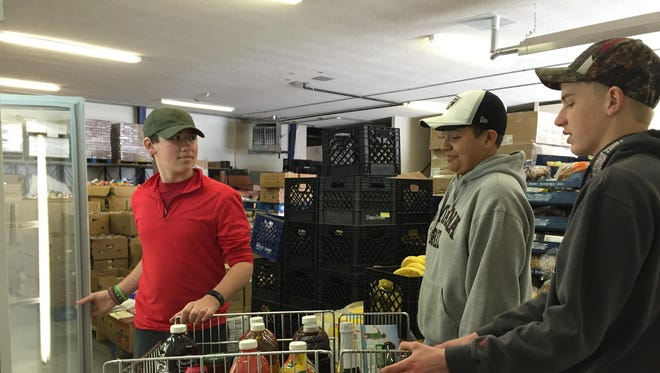 From left, Boy Scouts Sean Lynch, Taylor Willmarth and Colby Aderhold help sort and put away food at the Great Falls Community Food Bank warehouse Monday.