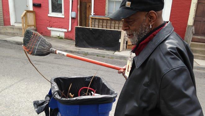 Leonard McKinney, 66, of York, shakes off his broom while cleaning up the first block of East Maple Street in York. McKinney works 15 hours each week through Crispus Attucks Senior Community Service Employment Program.
