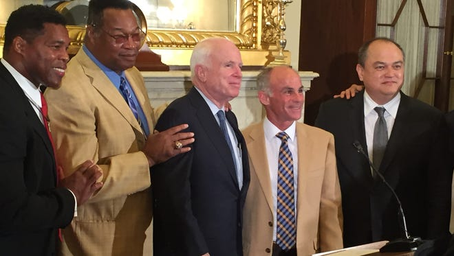 Arizona Sen. John McCain (center) hosted a news conference Tuesday with (from left) football star and fighter Herschel Walker and former heavyweight boxing champion Larry Holmes and others to announce the continuation of a study of the brain function of fighters.
