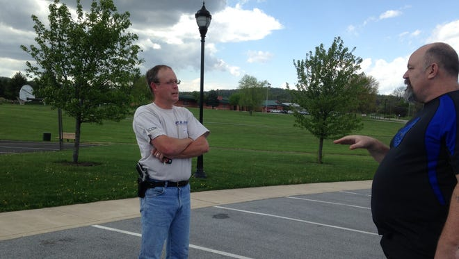 Jeff O'Brien, left, talks with John Weber about open carry gun laws in Pennsylvania outside the Conewago Township municipal building on Copenhaffer Road during Tuesday's primary.