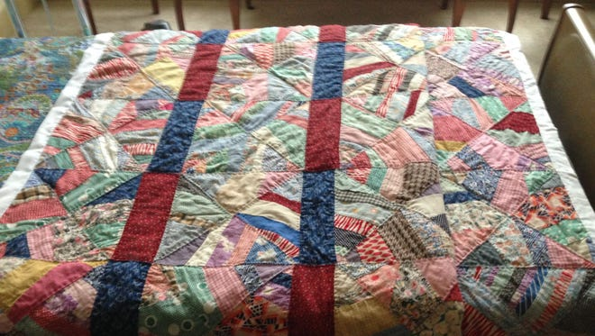 A quilt begun by Pat Godbold's mother at age 7 was recently finished by Pat's sister and how rests on mom's bed.