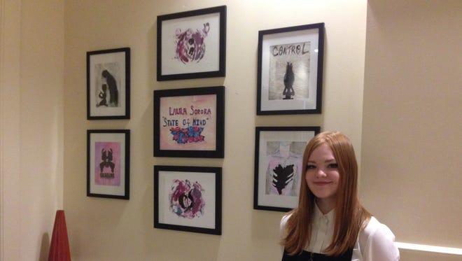 Dryden High School Senior Laura Soroka stands by her art work at the Seneca Place Gallery at Ithaca's Hilton Garden Inn.  Laura's art show is part of her work to raise awareness of mental health issues in teens as part of her Girl Scout Gold Award.