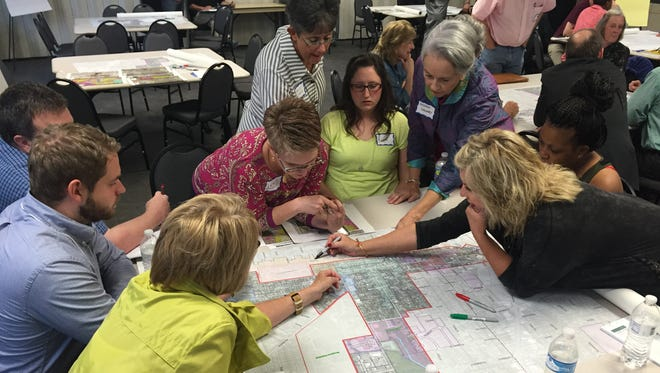A group of downtown Murfreesboro residents, business owners and stakeholders discuss a study area near North Highland Avenue during a workshop Monday night.
