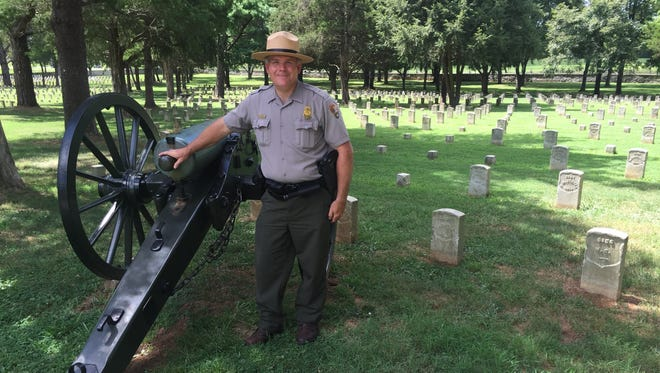 Stones River National Battlefield Park Ranger Jim Lewis stands by some of the gravestones.