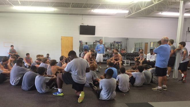 First-year USJ football coach Rusty Bradley talks with his players. Bradley has emphasized organization and attention to detail.