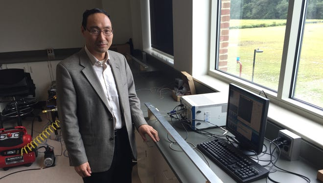 Yuanwei Jin, a University of Maryland Eastern Shore professor, poses beside his patented sensor system. The sensors, shown on far ends of a metal bar, could be used to help detect flaws in underground oil pipes, he suggests.