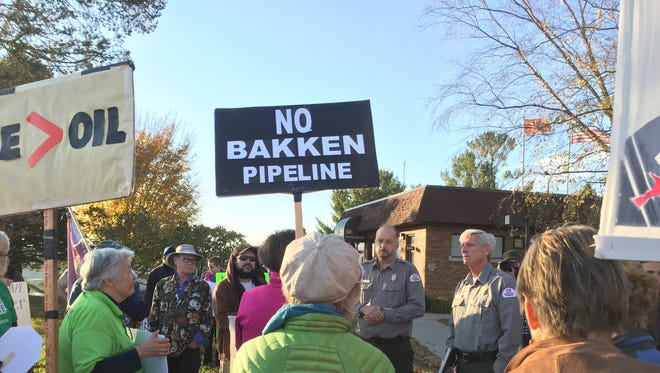 Rangers Doug Vogel, center left, and Jeff Peck, center right, speak with protesters opposing construction of the Dakota Access Pipeline who gathered Tuesday outside the Army Corps of Engineers office at the Coralville Dam.