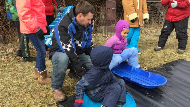 Cory Vanvalkenburgh, left, helps his son Hayden, 6, and Naomi MacQueen, 8, prepare to slide down a tarp-covered hill at Camp Cavell.
