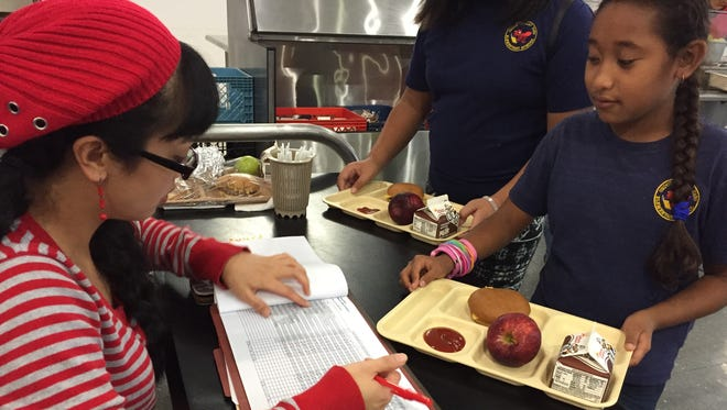 In this file photo, Ordot Chalan Pago Elementary School clerk Kimberly Jesus, left, checks the meal tray of Mio Damon, a fourth-grade student.