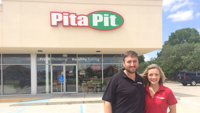 Matt and Alicia Smith stand outside their Pita Pit store in Shreve City. The couple plans to open their second location at the Kroger-anchored Camp Forbing Marketplace May 15.