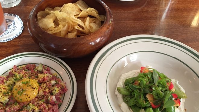 Beef tartare, left, and purslane and snap pea salad, right, from Longfellow bar in Over-the-Rhine
