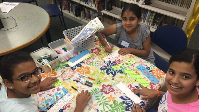 """Ananya Shinde, 11, of Montgomery; Vinuta Ramakrishnan, 9, of North Brunswick; and Aditi Deshmukh, 11, of Montgomery attended SCLSNJ's job shadowing program at the Mary Jacobs Memorial Library branch. During the pizza lunch, branch staff asked interns: """"What new thing did you learn about the library?"""" Shinde answered, """"I had no idea the library was so busy!"""""""