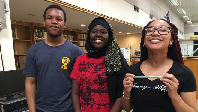 From left, De'aunte Johnson, Binti Mohamad and Tailor Davis. Davis is holding the control version of their experiment at the International Space Station.