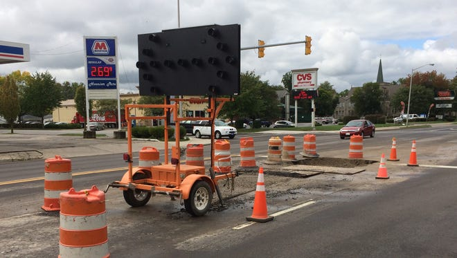 A sign directs traffic around a second hole dug for a second repair to the water system at 16th Street and East Main Street.