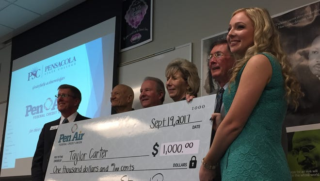 Taylor Carter, right, holds a ceremonial check for a $1,000 scholarship from Pensacola State College on Tuesday, Sept. 19, 2017. Stu Ramsey, Pen Air Federal Credit Union president and CEO, holds the check on the left.