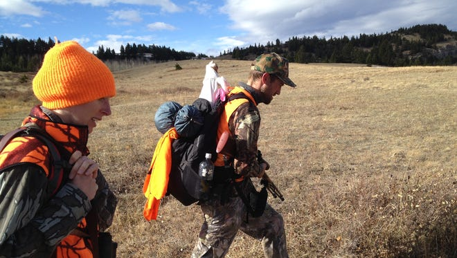 In this 2013 file photo, hunters Mary and Bob Ellenbecker, of Missoula, haul elk quarters after a member of their hunting party found success during the second week of the hunting season along the Rocky Mountain Front. A report says 1.5 million acres of federal land in Montana is surrounded by private land and inaccessible without permission.