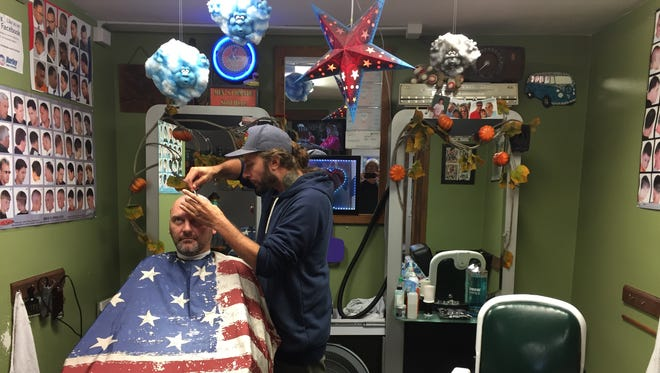 Daniel Hurley shaves customer Elwood Smith's head at his shop on the main drag of Mount Holly Springs. He wasn't surprised by the news that Sayfullo Saipov had been pulled over for failing a truck inspection, saying the borough police pull trucks over all the time.