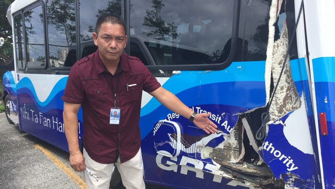 Guam Regional Transit Authority Transportation Supervisor Mark Crisostomo shows the damage on a bus involved in an accident in December 2016 at the Department of Public Works compound in Tamuning on Nov. 3, 2017.  The bus is one of several that GRTA can't use for busing because the agency doesn't have a maintenance contract.
