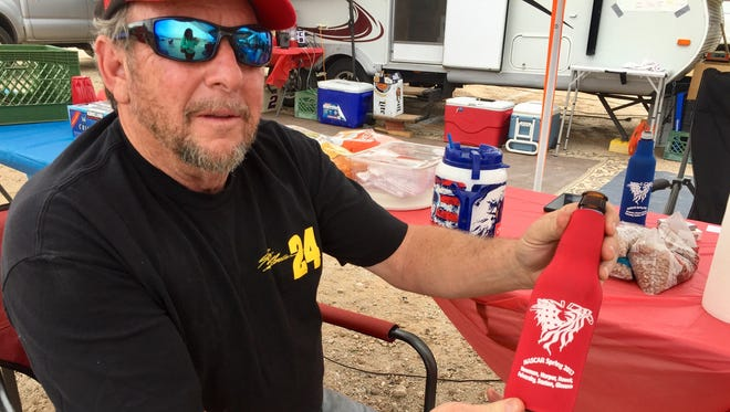 Dewayne Saxton, a Linden, Arizona, resident holds up the custom koozie his group makes every year for the NASCAR race weekends at Phoenix International Raceway in Avondale.