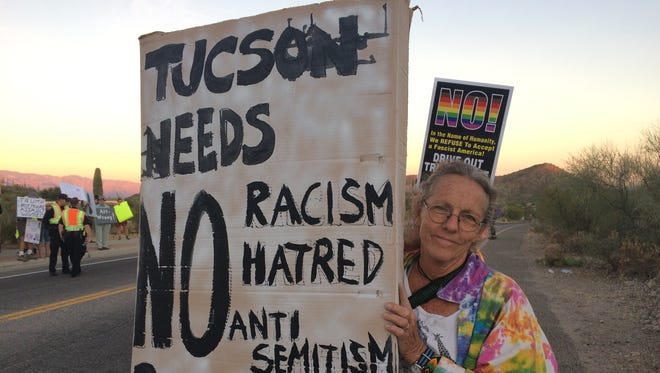 """A female protester holds a sign that reads """"Tucson needs no racism, hatred, anti-semitism, Bannon"""" outside the J. W. Marriott Starr Pass Tucson where former White House strategist Steve Bannon  was set to speak on Nov. 18."""
