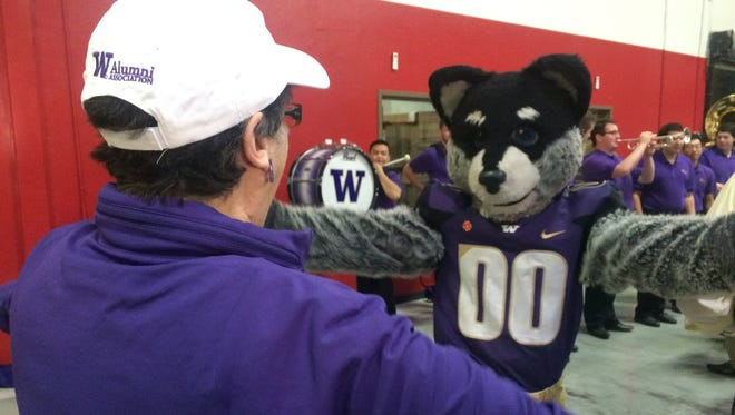University of Washington President Ana Mari Cauce hugs mascot Harry the Husky during a volunteering event at St. Mary's Food Bank on Dec. 29, 2017. Fans from Washington and Penn State volunteered together the day before their Fiesta Bowl matchup.