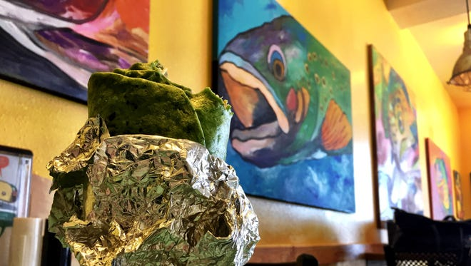 A fish supreme burrito with a spinach wrap is served at Taco del Sol.