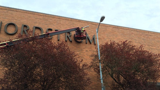 Workers begin removing the sign on the Nordstrom building in downtown Salem.