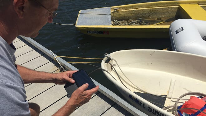 Rick Lane, a retired Indian River County Sheriff's Office captain, leans down to take a picture of an expired state boat registration sticker April 30, 2018, at the Vero Beach Municipal Marina.