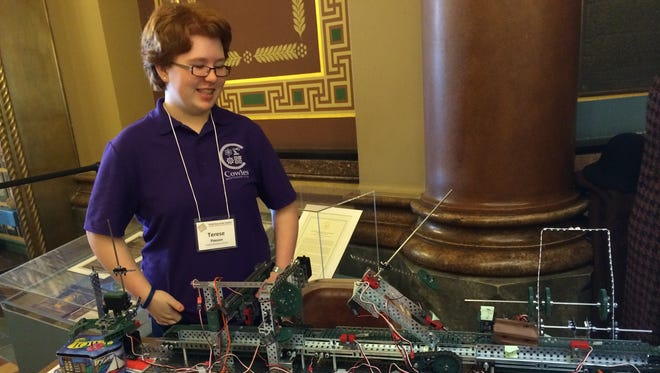 Terese Paxton, 14, of Cowles Montessori School shows off an assembly line she and a classmate built for the sixth STEM Day at the Capitol on Thursday.