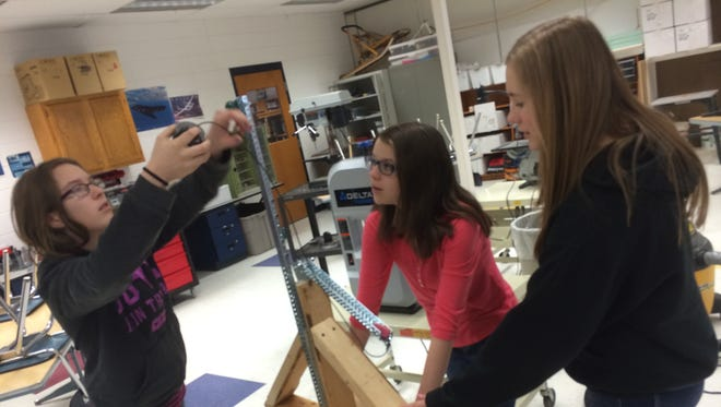 Mosinee Middle School eighth graders Maddy Barber, Kinsey Miller and Emily Napiwocki demonstrate a trebuchet they and their classmate Delphine Hintz collaborated on. They built the trebuchet to mimic a casting motion.